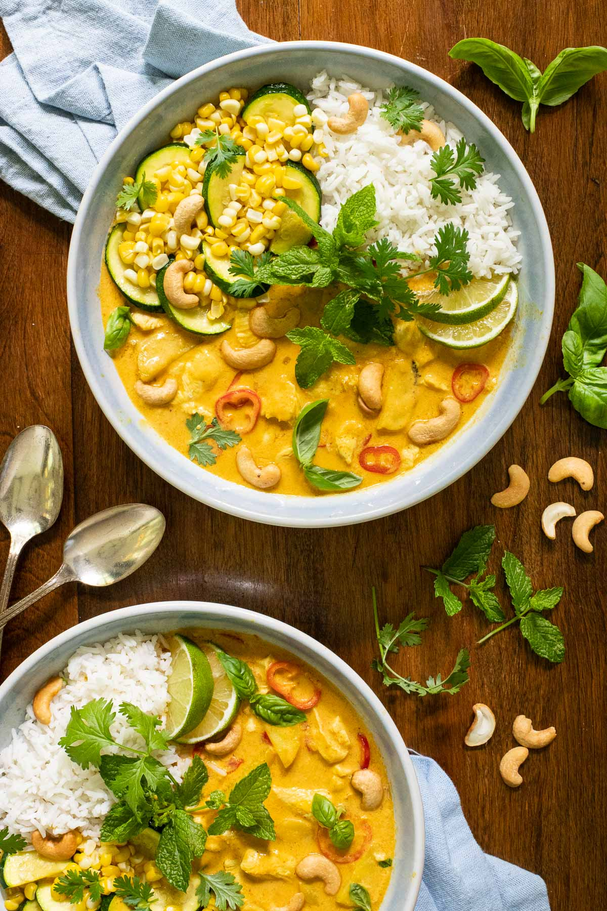 Overhead vertical photo of Summery Chicken Coconut Curry in light blue serving bowls on a wooden table.