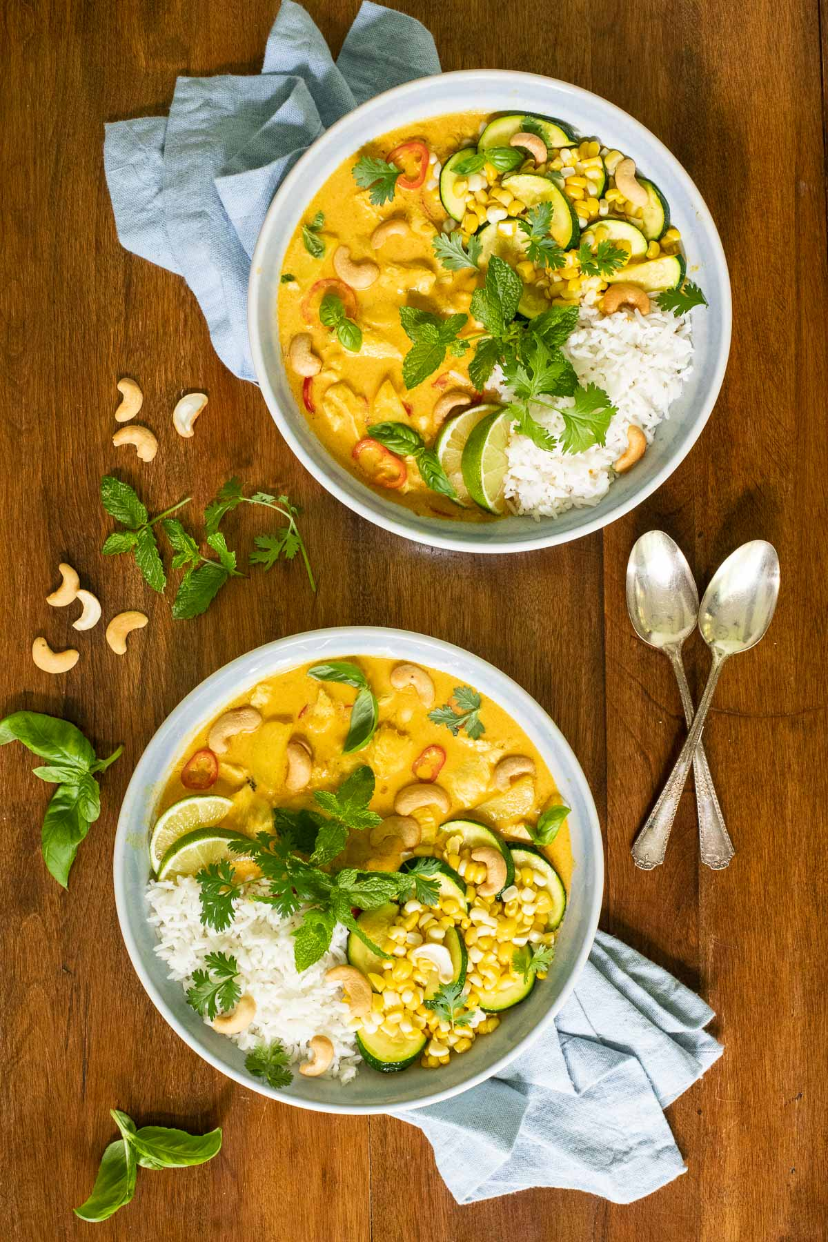 Overhead vertical photo of Summery Chicken Coconut Curry in individual white serving bowls on a wooden table.