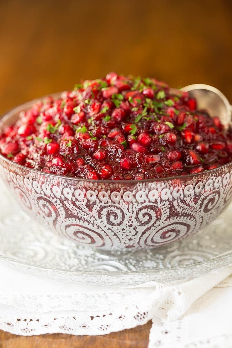 Close up vertical photo of a Super Easy Cranberry Pomegranate Sauce in an etched glass serving bowl.