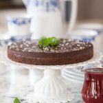 Vertical picture of Swedish Chocolate Sticky Cake on a white cake stand with a small glass cruet of raspberry sauce