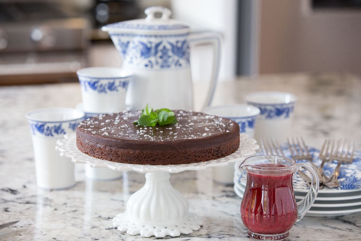Photo of a Swedish Sticky Chocolate Cake (Kladdkaka) on a granite kitchen counter with a blue and white serving set in the background and a glass serving pitcher of raspberry coulis in the right foreground.