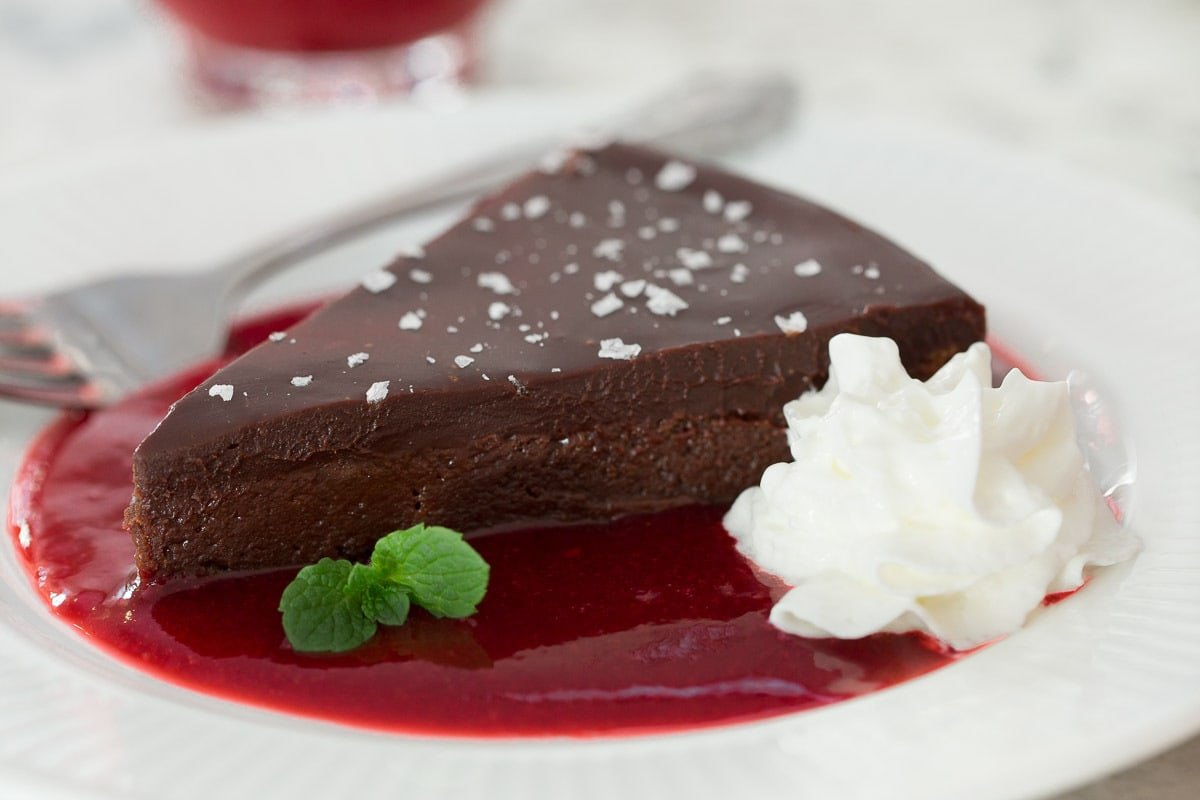 Photo of a slice of Swedish Chocolate Sticky Cake served a plate in a pool of raspberry coulis and a dollop of whipped cream.