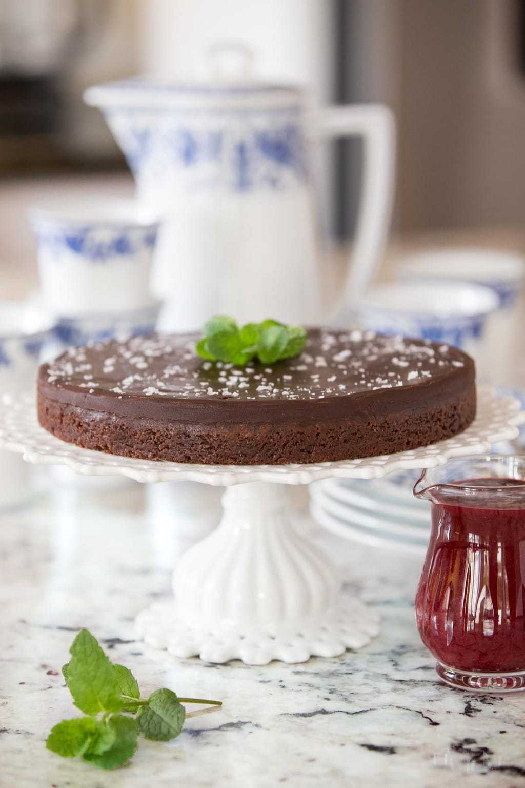 Vertical photo of a Swedish Chocolate Sticky Cake on a white cake stand with a small glass cruet of raspberry sauce nearby.