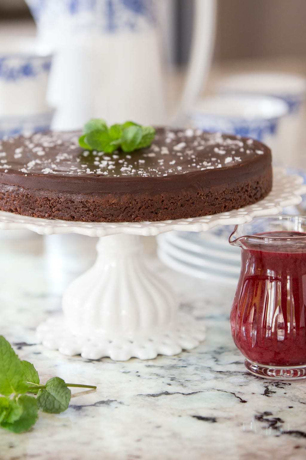 Vertical photo of Swedish Sticky Chocolate Cake on a white pedestal cake stand garnished with mint leaves.