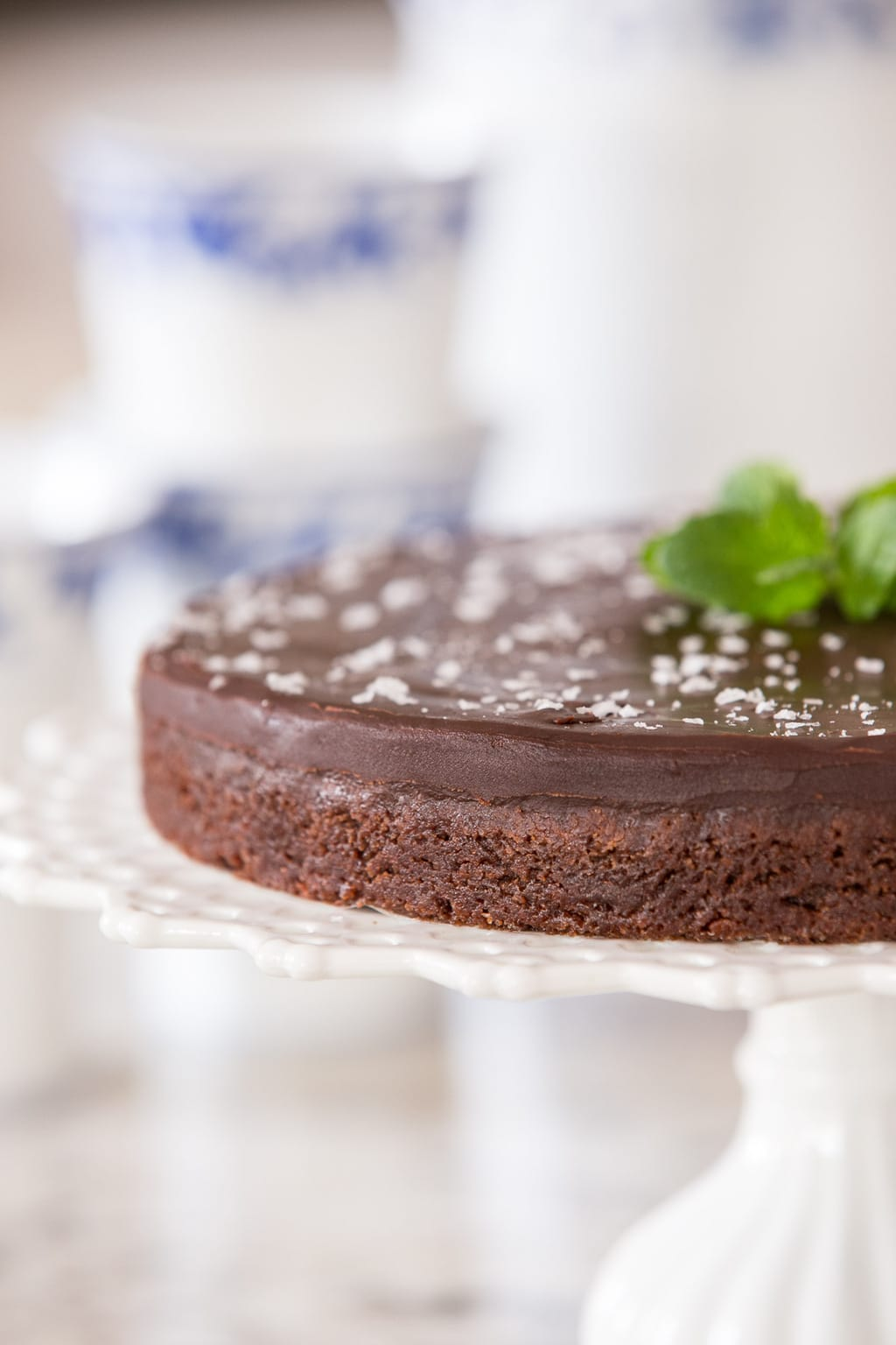 Photo of a Swedish Sticky Chocolate Cake (Kladdkaka) on a white cake pedestal stand garnished with a sprig of fresh mint.