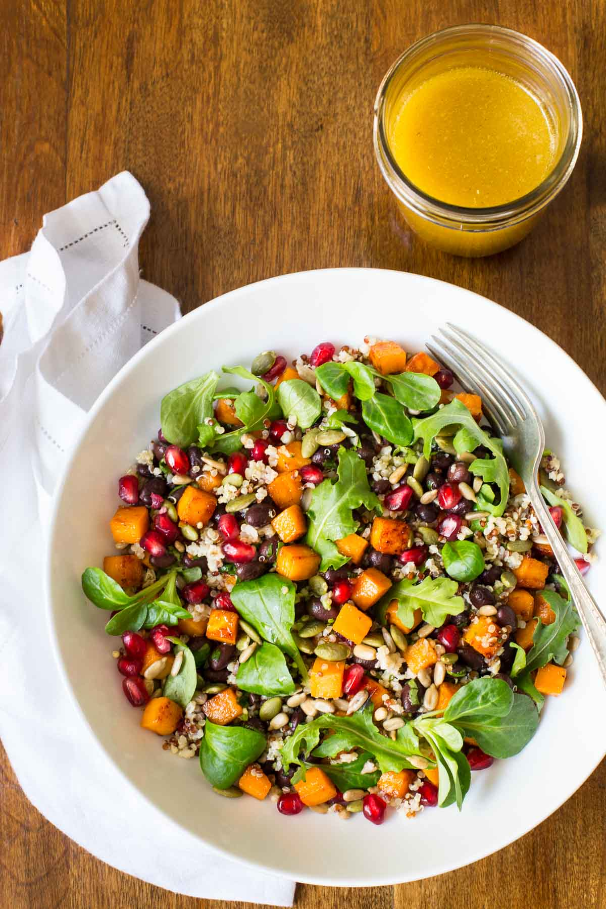 Vertical overhead picture of Sweet Potato Quinoa Salad in a white bowl with a jar of dressing
