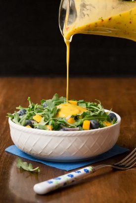 Vertical picture of a green salad in a white bowl with mango dressing poured on top