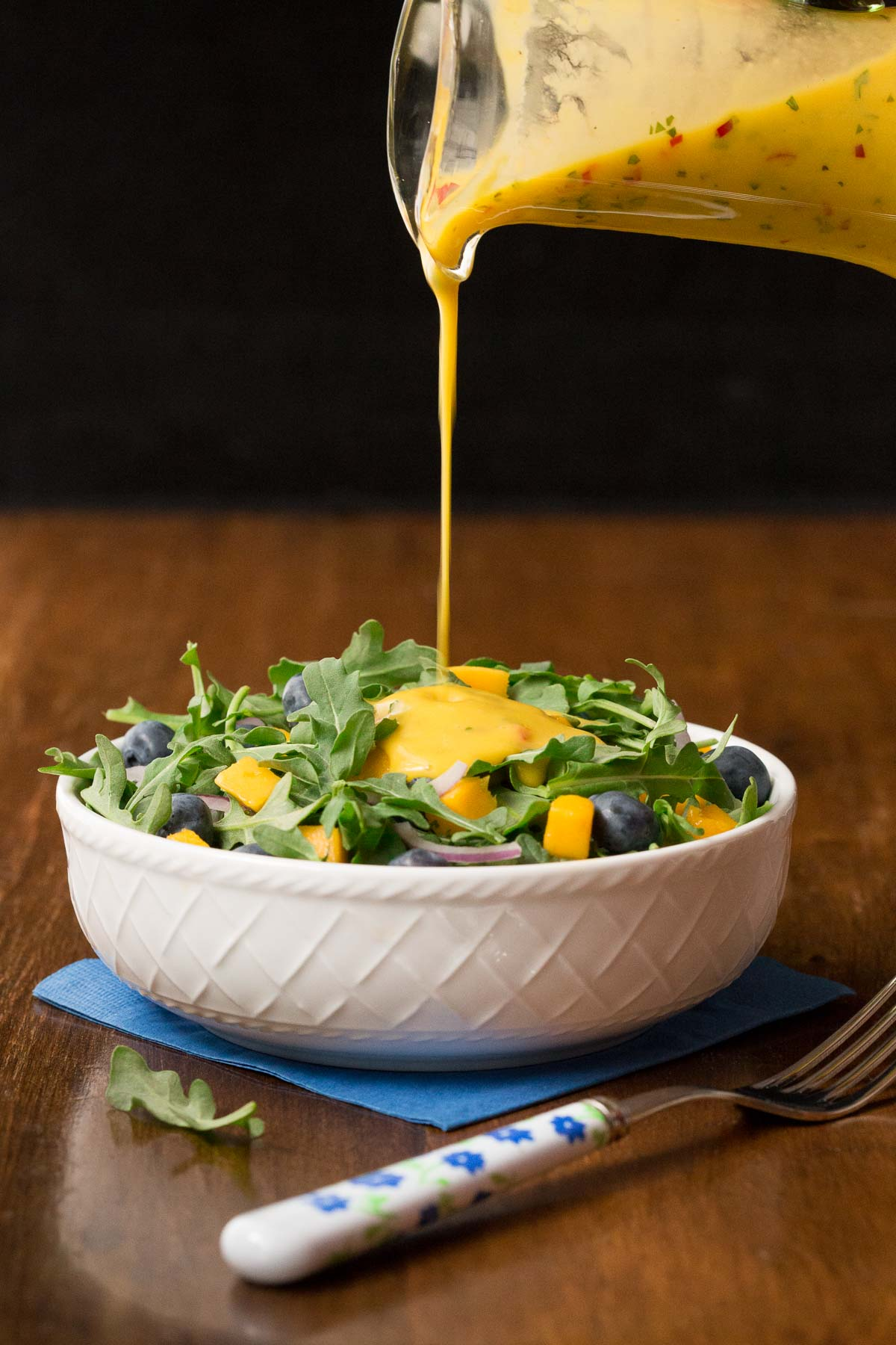 Photo of Sweet and Spicy Mango Salad Dressing being poured from a glass carafe over a salad on a wood table.