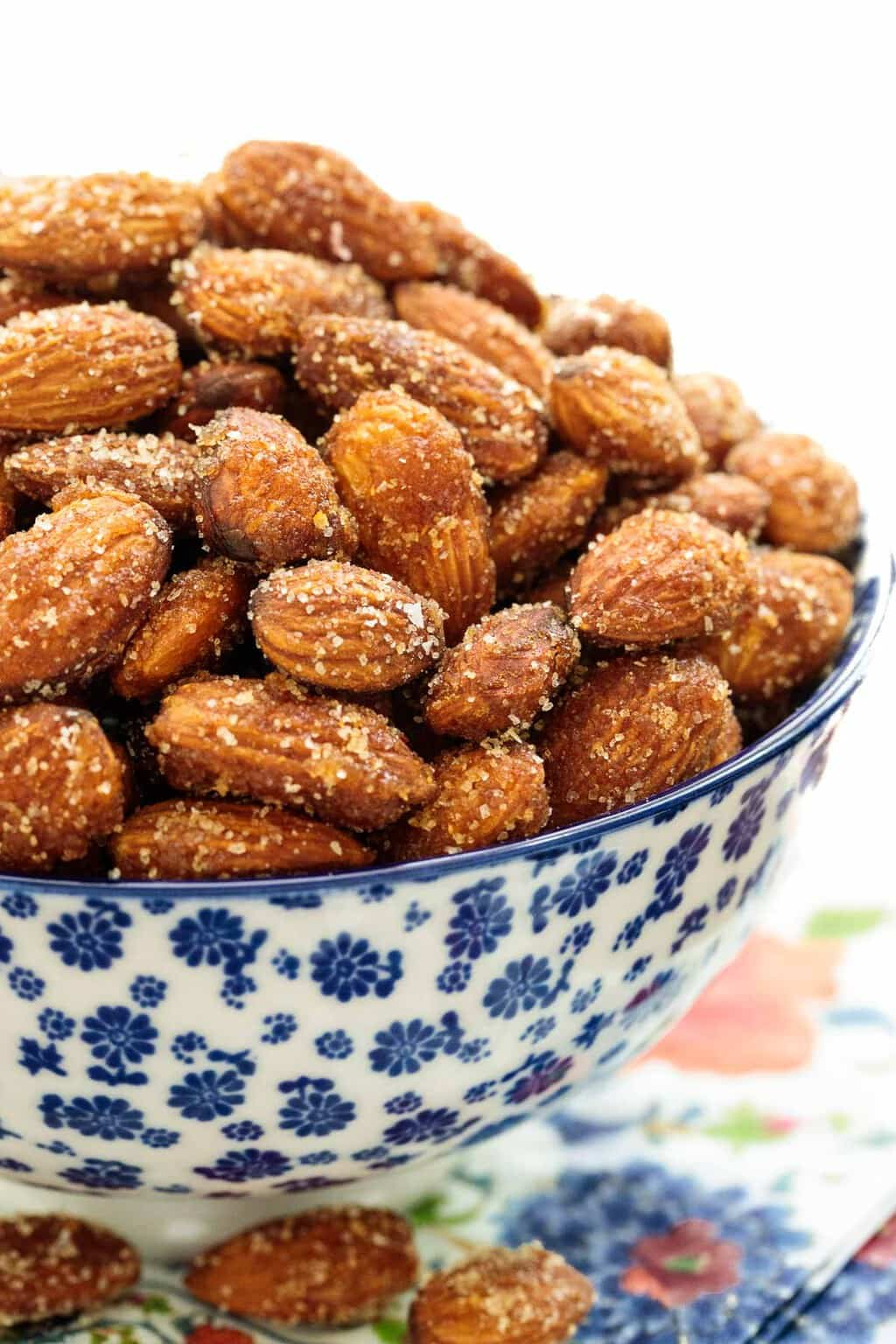 Closeup of a blue and white patterned bowl filled with Sweet and Spicy Roasted Almonds on a colorful patterned napkin.