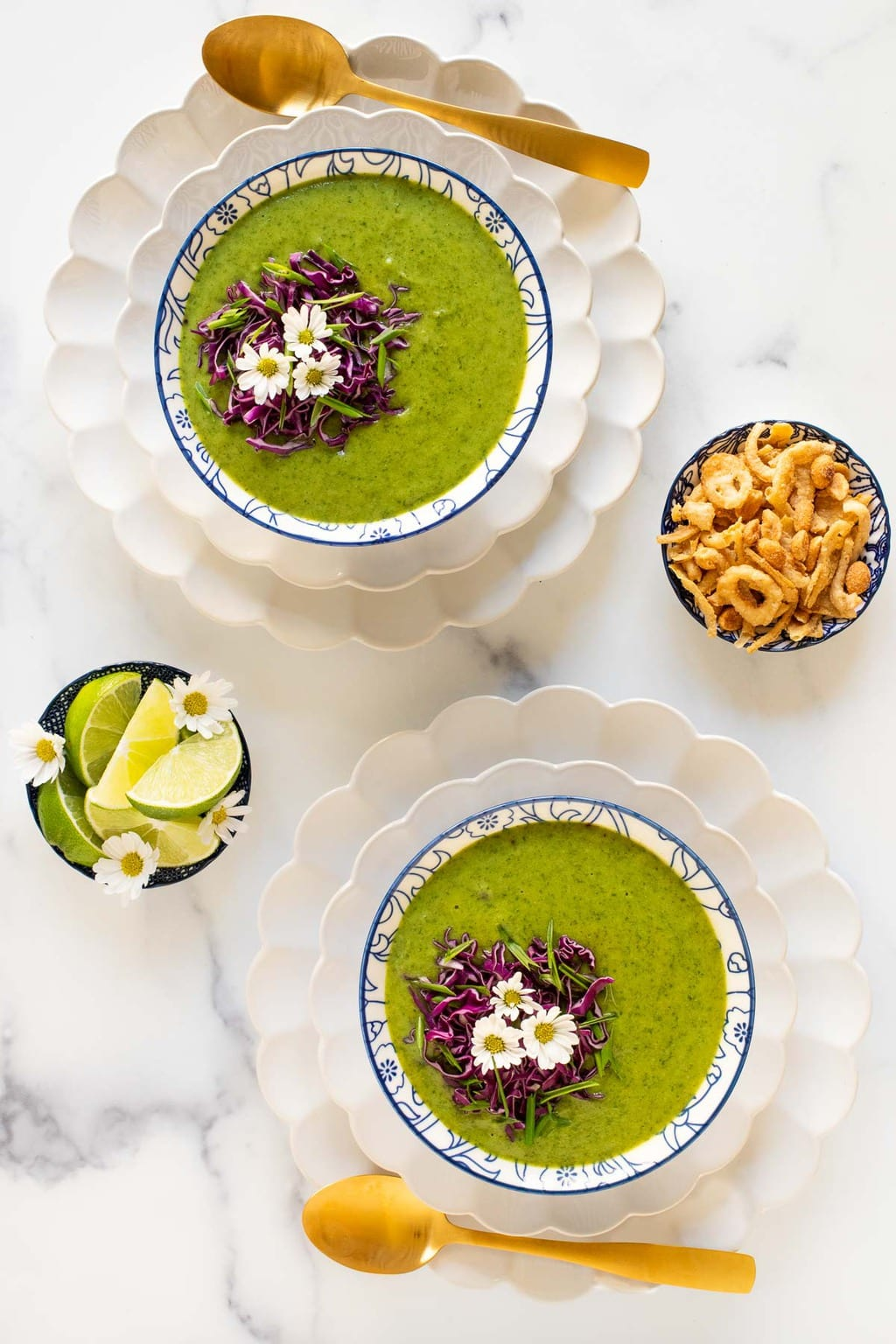 Overhead vertical photo of bowls of Thai Broccoli Spinach Soup on white scalloped plates.
