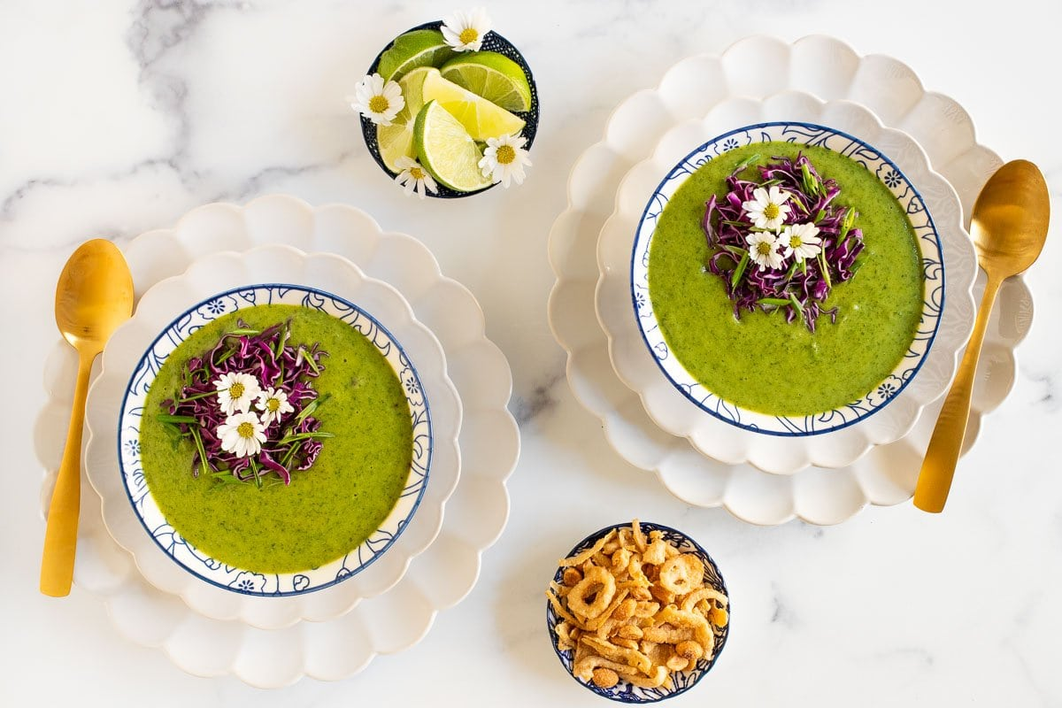 Horizontal overhead photo of bowls of Thai Broccoli Spinach Soup on a white marble surface.