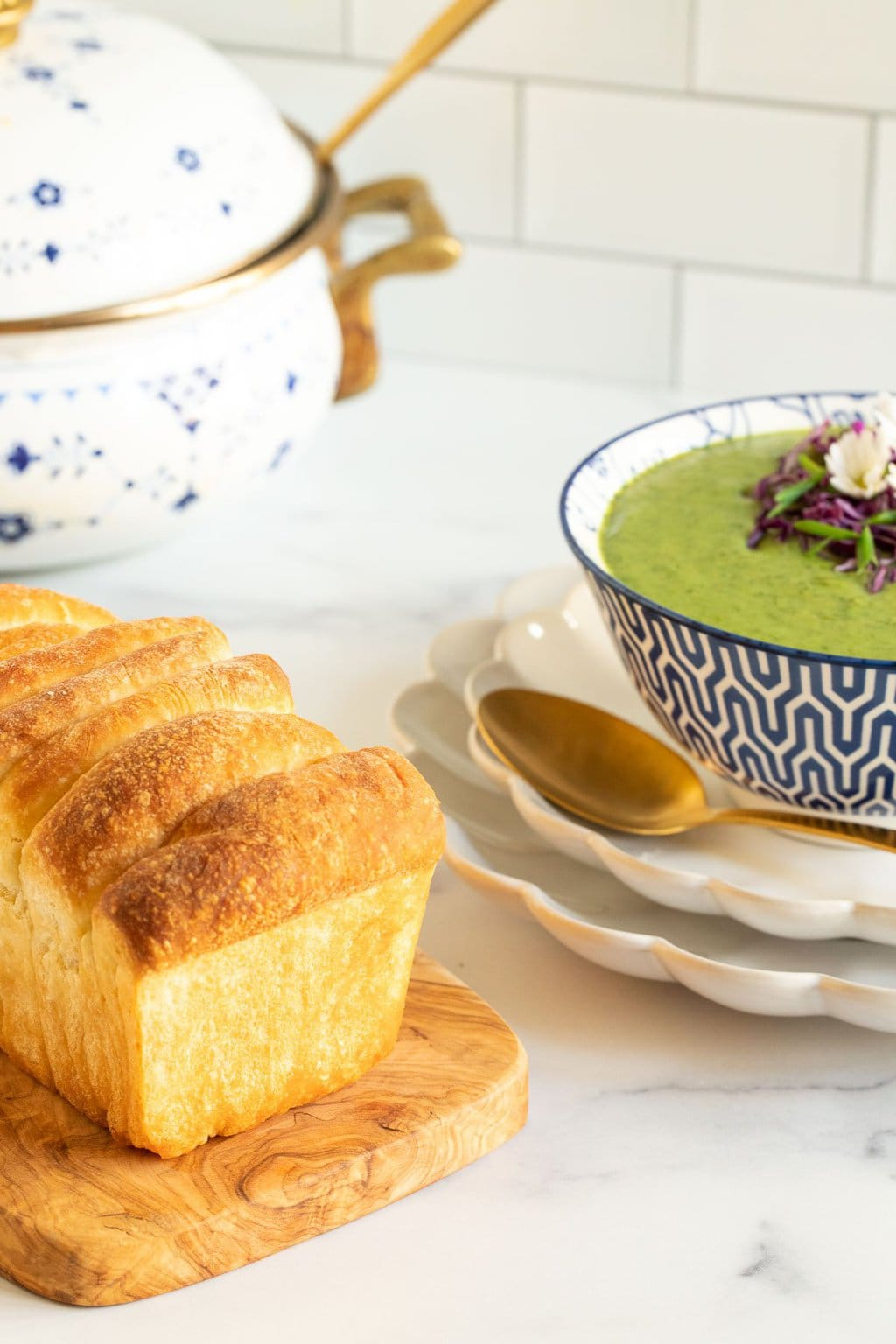 Vertical photo of a bowl of Thai Broccoli Spinach Soup with homemade pull apart bread in the foreground.