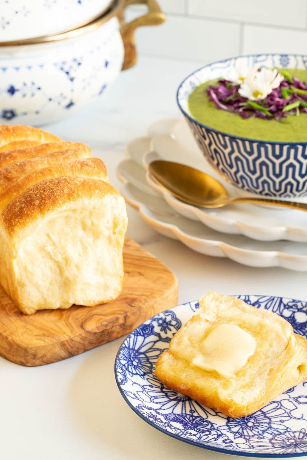 Vertical photo of a loaf of No Knead Pull-Apart Brioche Bread with a slice of the bread buttered on a blue and white patterned individual serving plate. A bowl of Thai Broccoli Spinach Soup is in the background.
