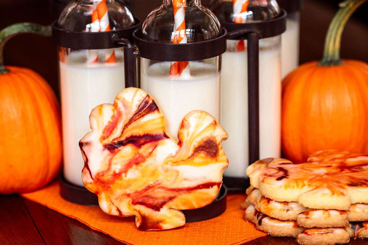 Photo of Easy Thanksgiving Shortbread Cookies with pumpkins and bottles of milk in the background.