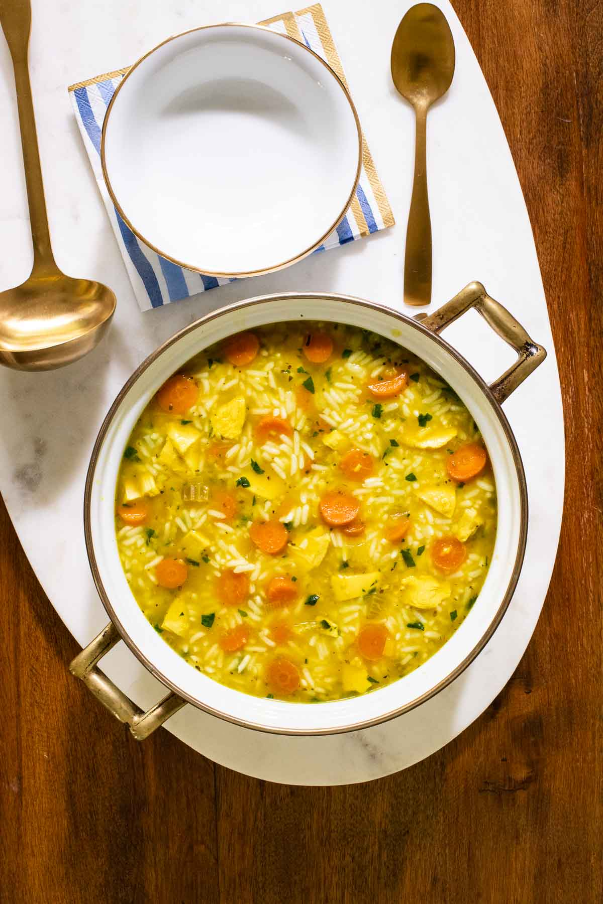Overhead vertical photo of a pot of The BEST Chicken and Rice Soup on an oval marble surface