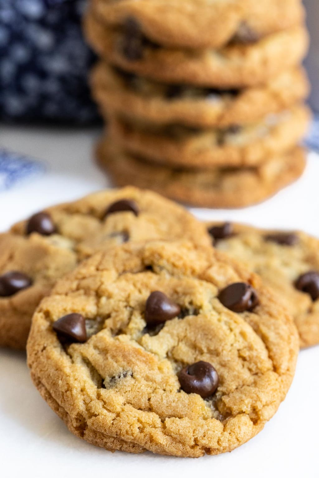Closeup vertical photo of a batch of The BEST Chocolate Chip Cookies with a stack of the cookies in the background.