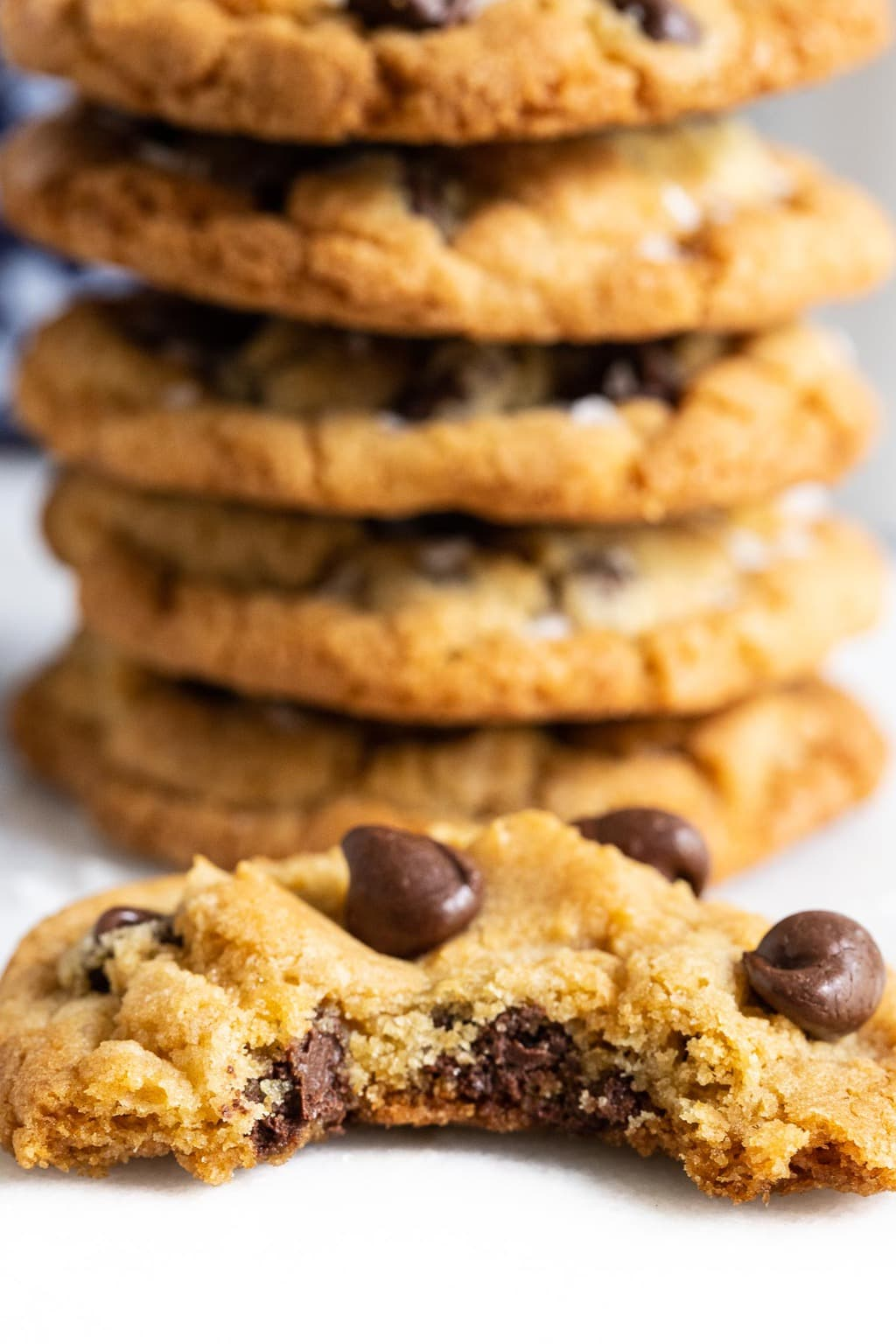 Ultra closeup vertical photo of the inside of one of The BEST Chocolate Chip Cookies with a stack of cookies in the background.