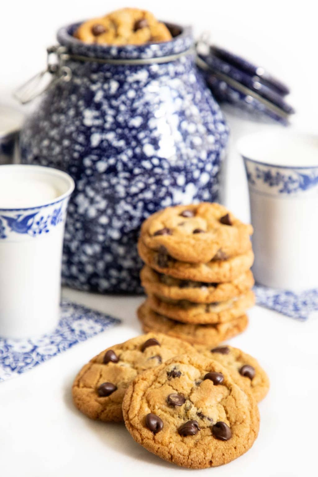 Vertical photo of a batch of The BEST Chocolate Chip Cookies next to blue and white patterned milk cups and a cookie jar.