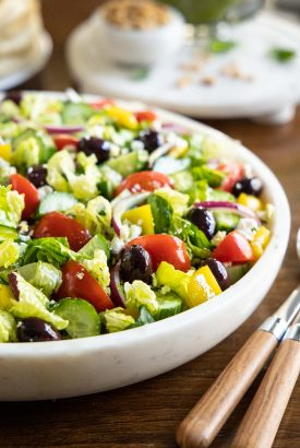 Vertical closeup photo of The BEST Greek Salad in a marble serving bowl.