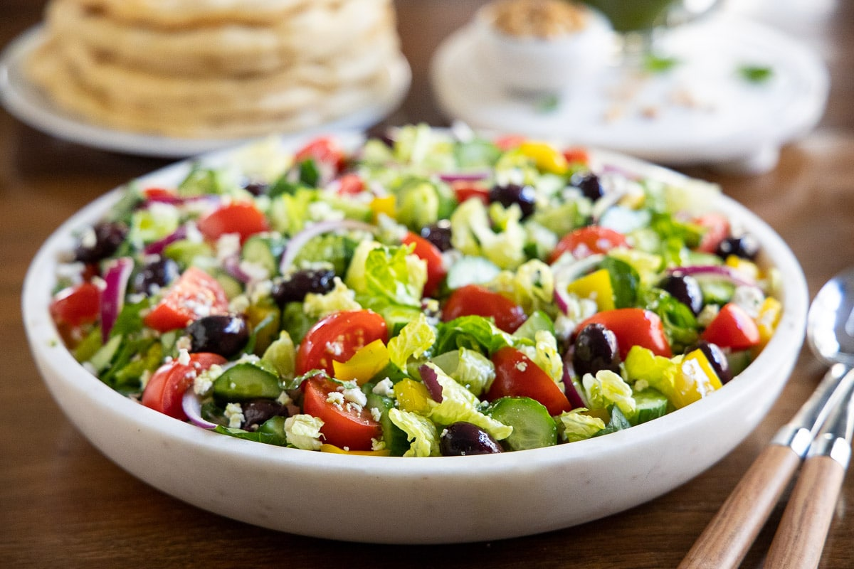 Horizontal closeup photo of The BEST Greek Salad in a white marble serving bowl on a wood table.