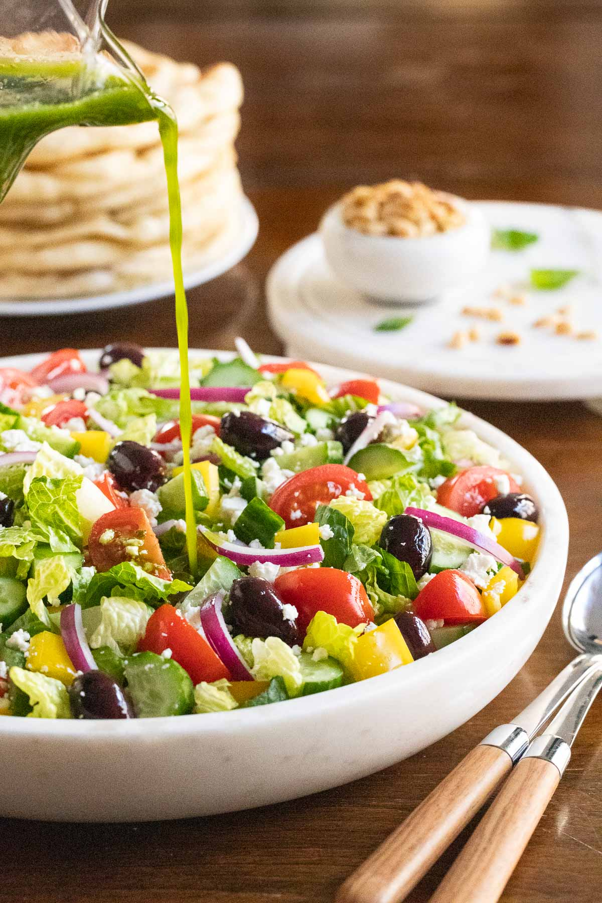 Vertical photo of The BEST Greek Salad in a white marble serving bowl with Greek Salad Dressing being poured on the salad.