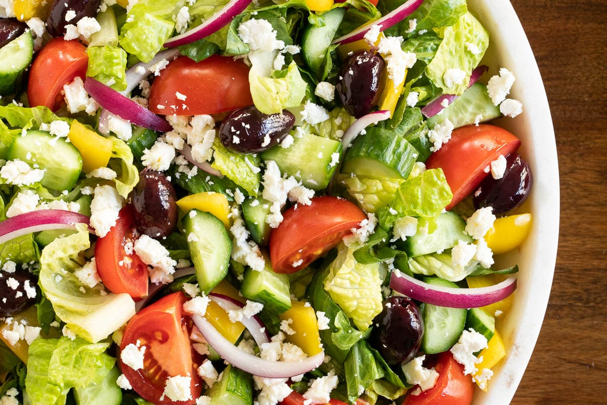 Overhead closeup photo of The BEST Greek Salad in a white marble serving bowl.