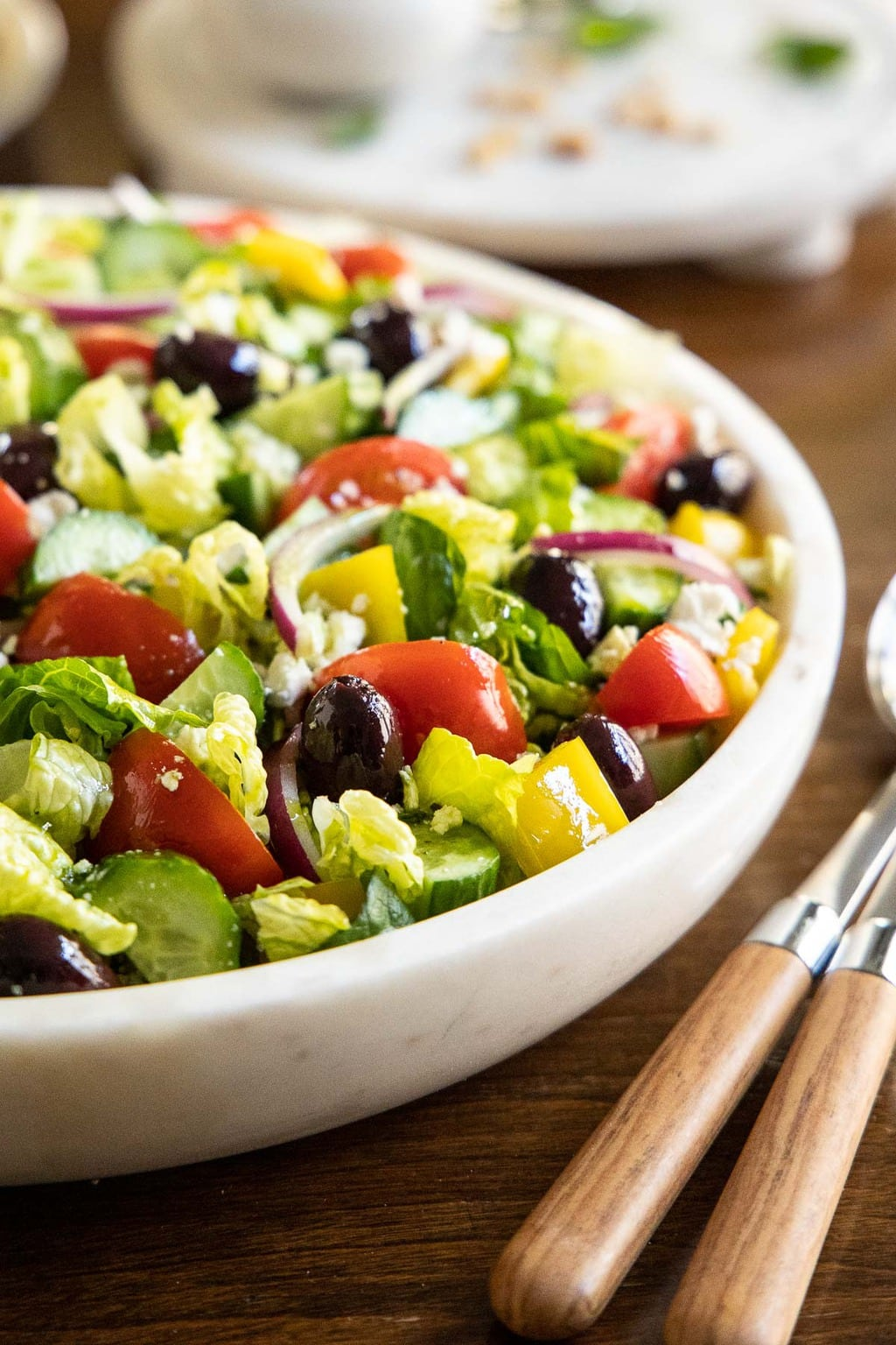 Vertical closeup photo of The BEST Greek Salad in a white marble serving bowl on a wood table.