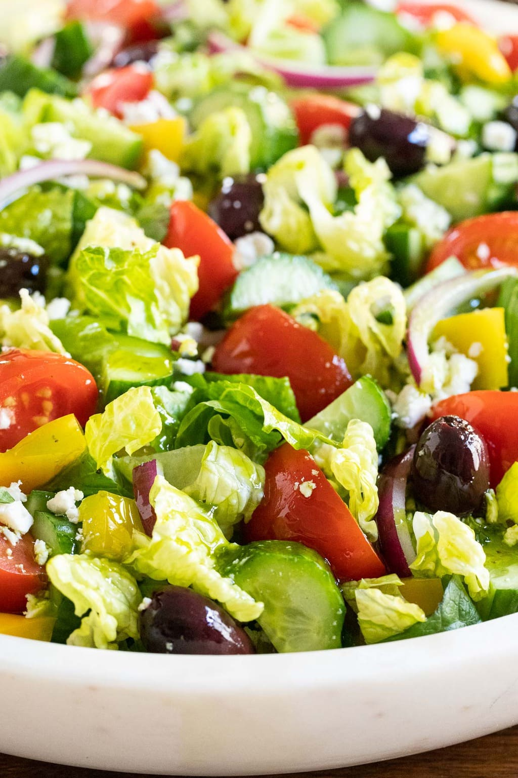Vertical closeup photo of The BEST Greek Salad in a white marble serving bowl.