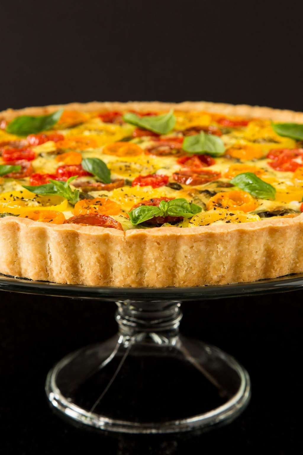 Vertical photo of a Tomato Basil and Fresh Mozzarella Tart on a glass pedestal stand against a black background.