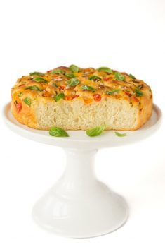 Vertical picture of Tomato, Basil, Parmesan Focaccia on a white stand on a white background