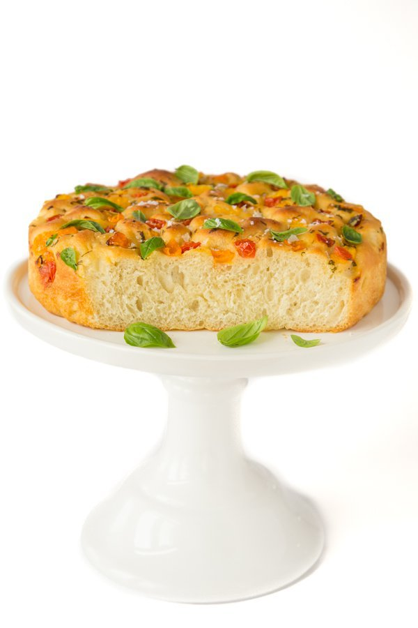 Vertical photo of a Tomato Basil Parmesan Focaccia bread on a white stand against a white background.