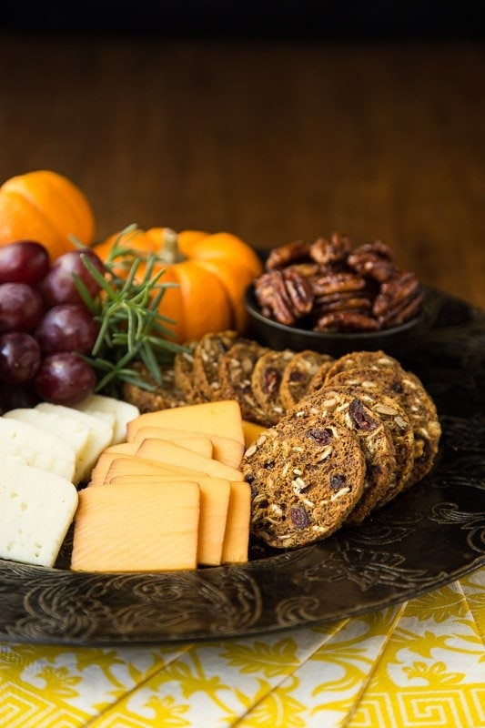 Vertical picture of Trader Joe's Pumpkin Cranberry Crisps in a platter with cheese, grapes, nuts and pumpkins