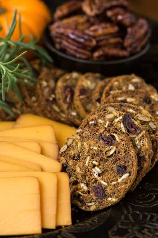 Closeup photo of an appetizer platter of Copycat Trader Joe's Pumpkin Cranberry Crisps with cheese, mini-pumpkins and pecans, garnished with a sprig of rosemary.