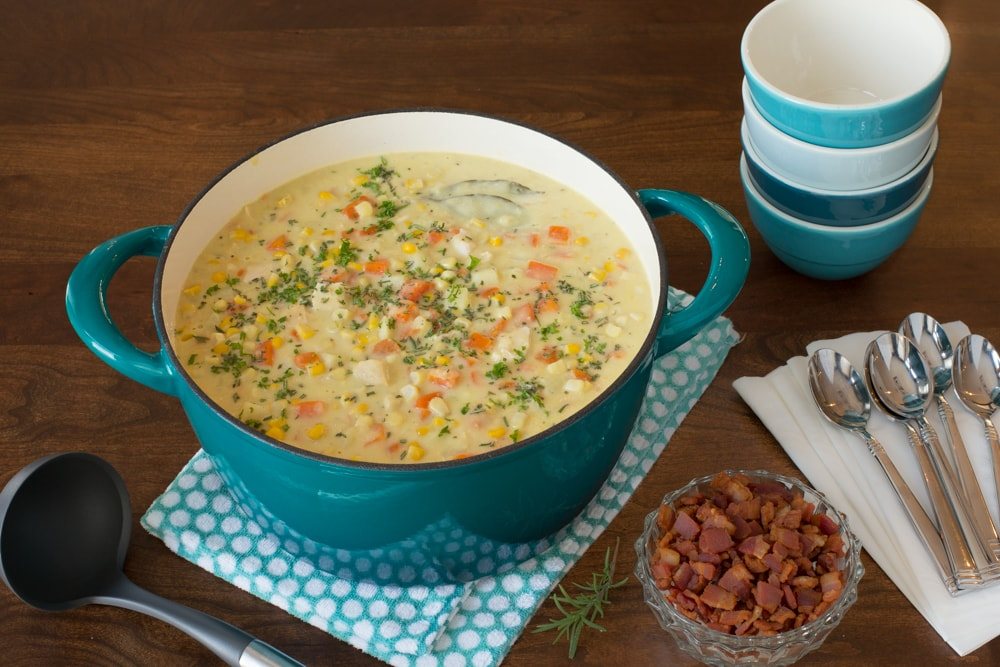 Overhead view of Turkey Corn Chowder in a turquoise dutch oven and a stack of bowls