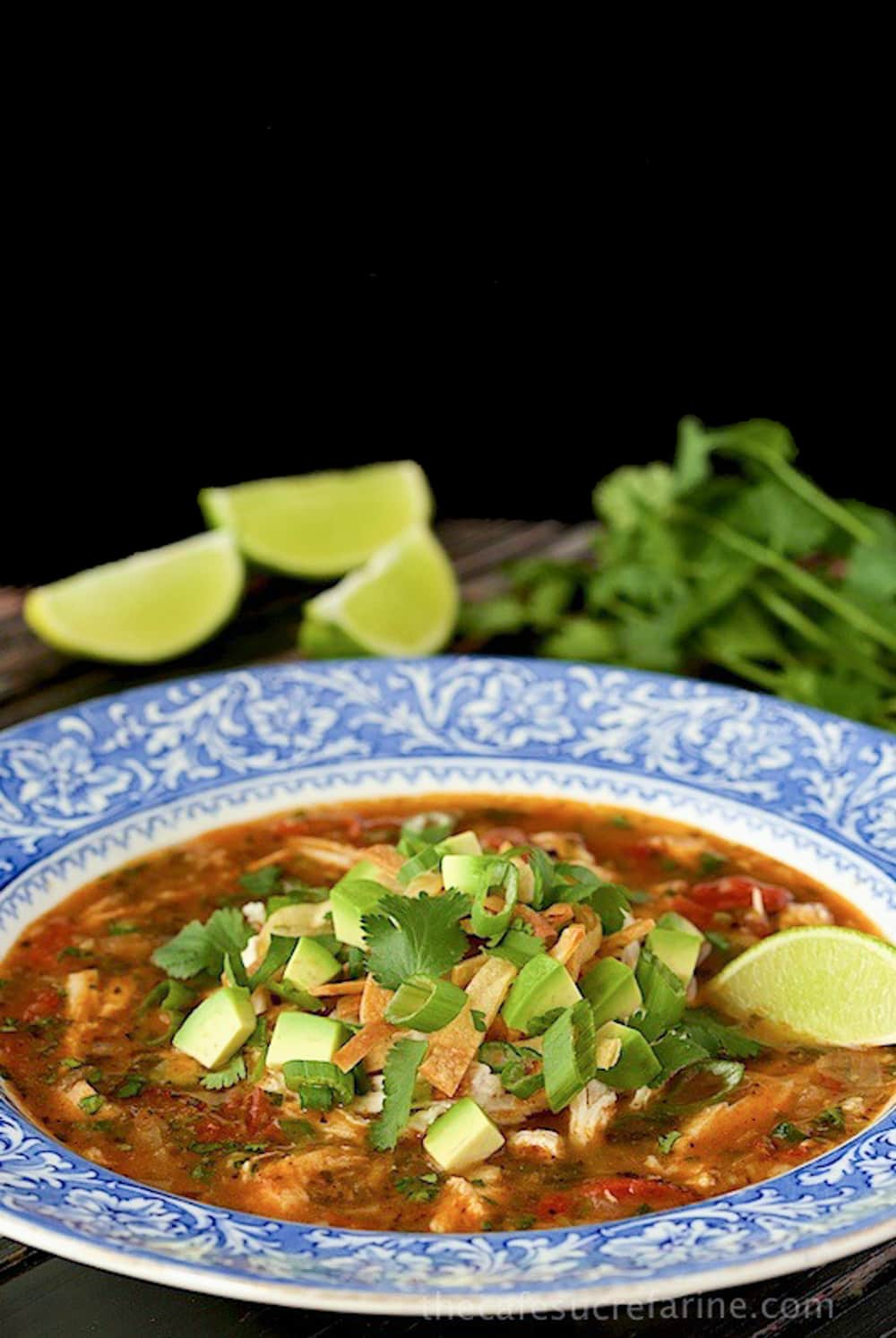 Vertical picture of turkey tortilla soup in a blue and white bowl on a black background