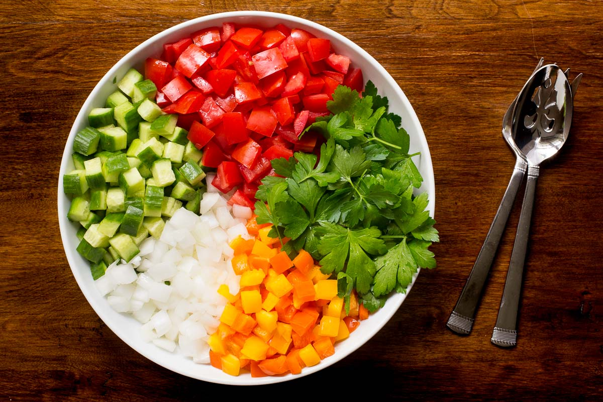 Overhead photo of a white dish filled with the ingredients used to make Turkish Tomato Cucumber Salad.