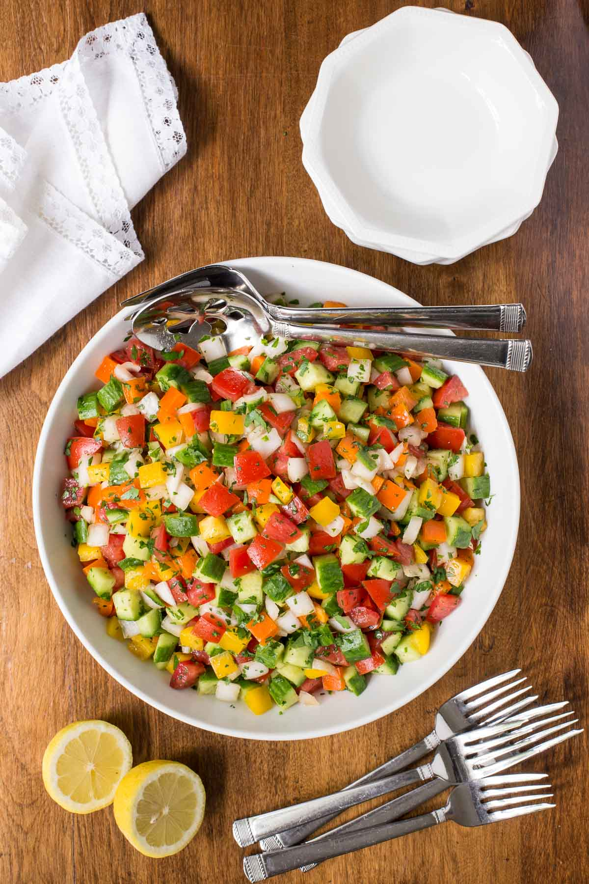 Overhead photo of a dish of Turkish Tomato Cucumber Salad, surrounded by a napkin, individual serving bowls, lemons and silverware.