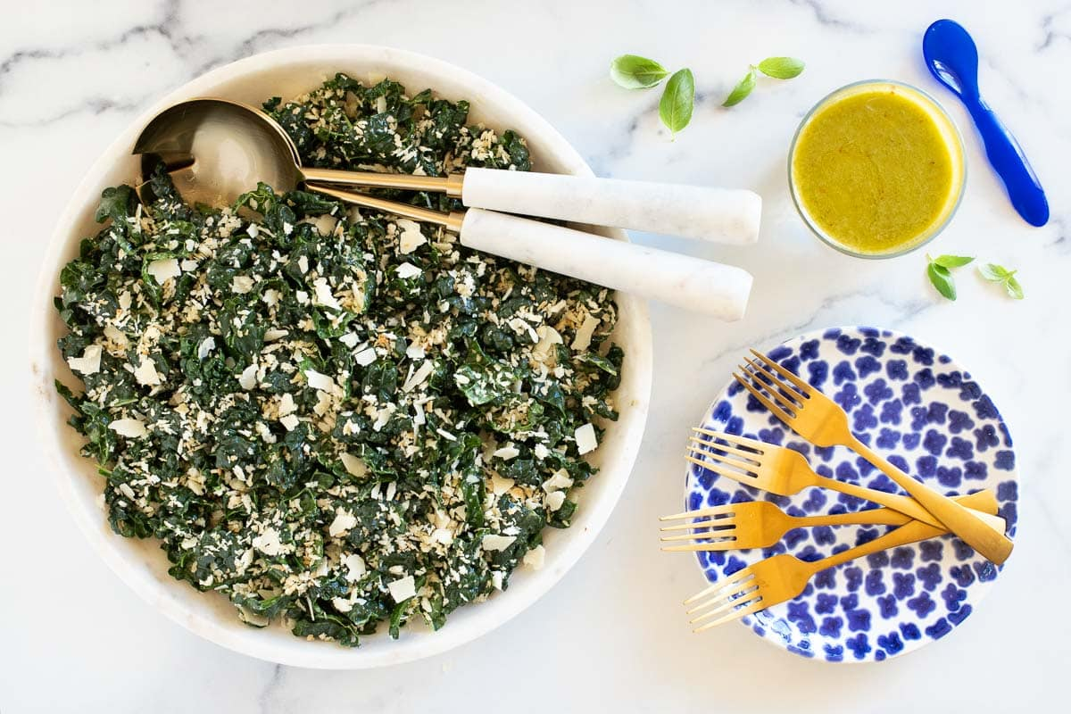 Horizontal overhead photo of a Tuscan Kale Salad with Lemon Basil Dressing on a white marble surface.