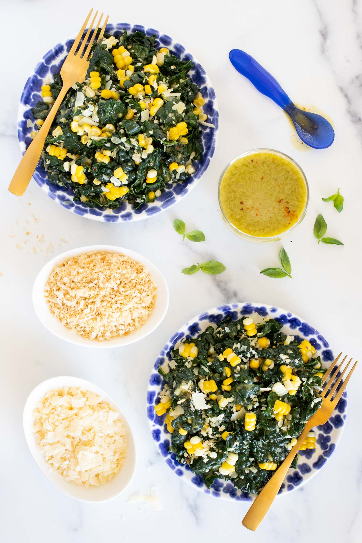 Vertical overhead photo of a Tuscan Kale Salad with Lemon Basil Dressing on a white marble surface.