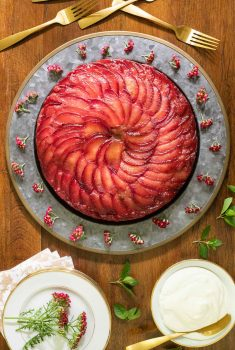 Vertical overhead picture of Upside Down Plum Cake on a platter with white dessert plates and flowers