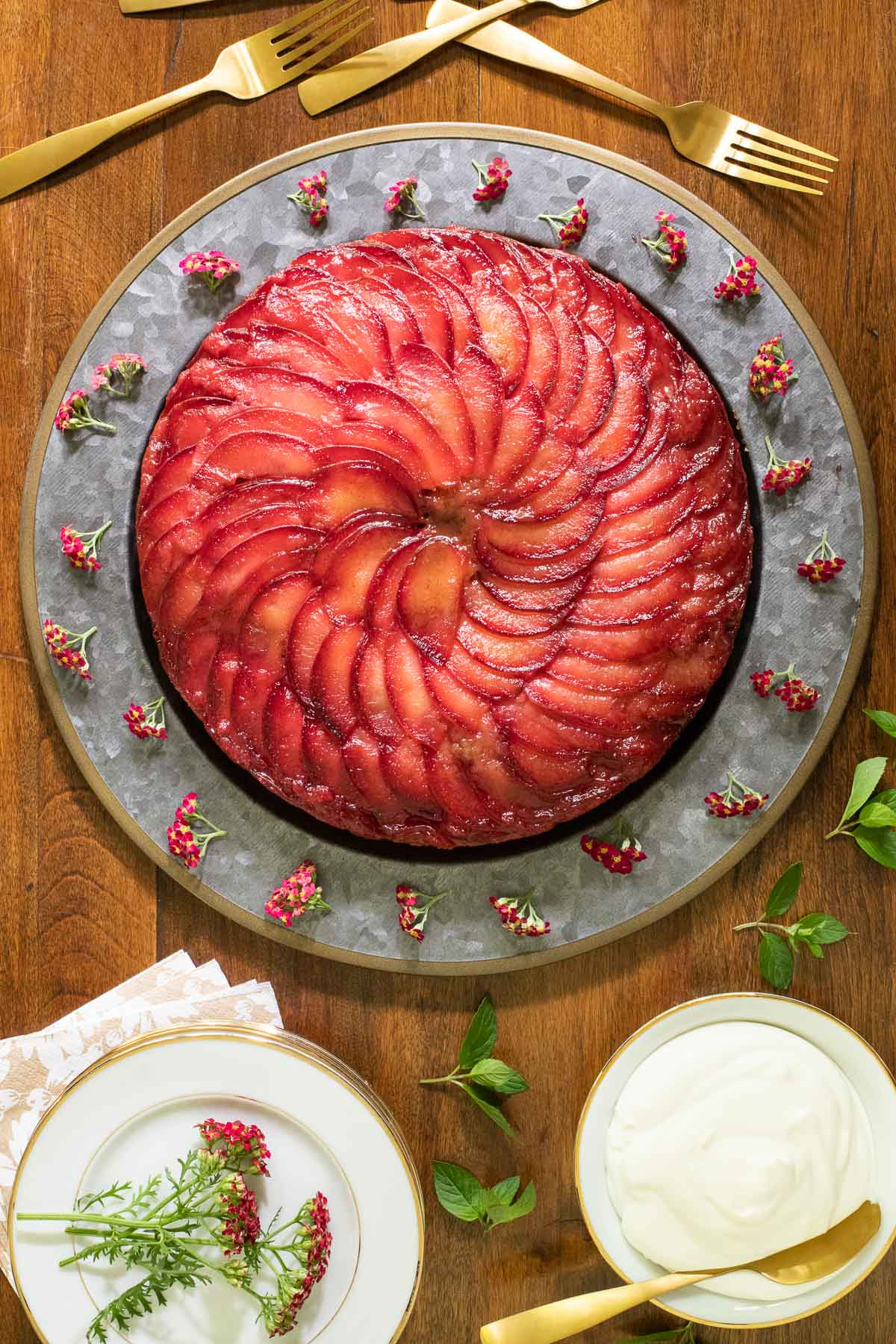 Overhead vertical photo of a Upside Down Plum Cake on a galvanized charger plate.