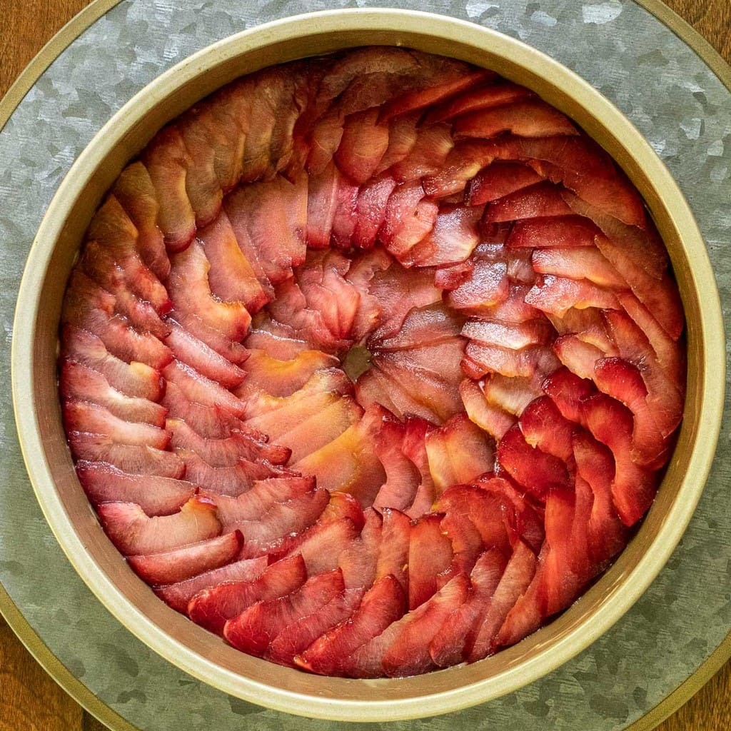 Overhead vertical photo of sliced plums being prepped for making a Upside Down Plum Cake.