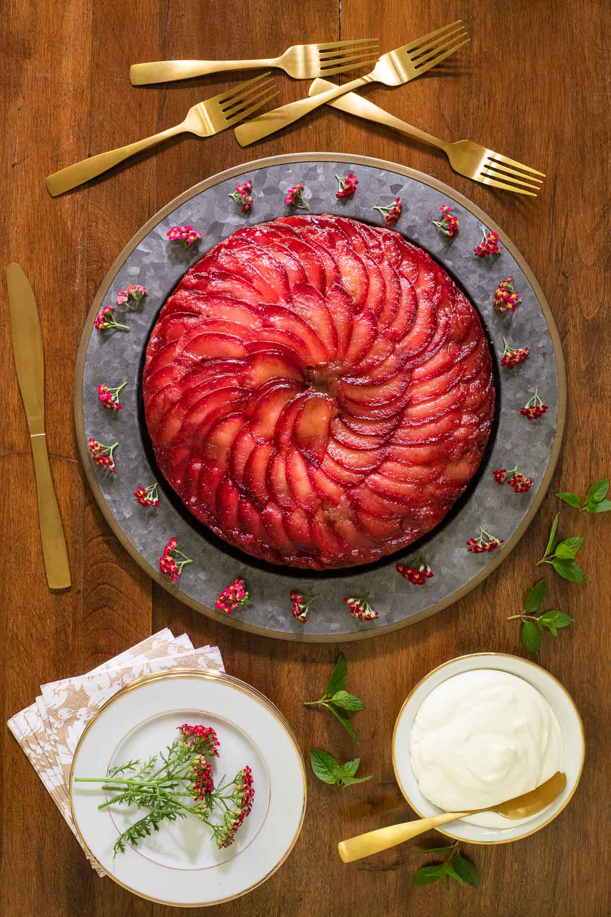 Vertical overhead photo of a Upside Down Plum Cake - on a steel charger plate surrounded by gold utensils