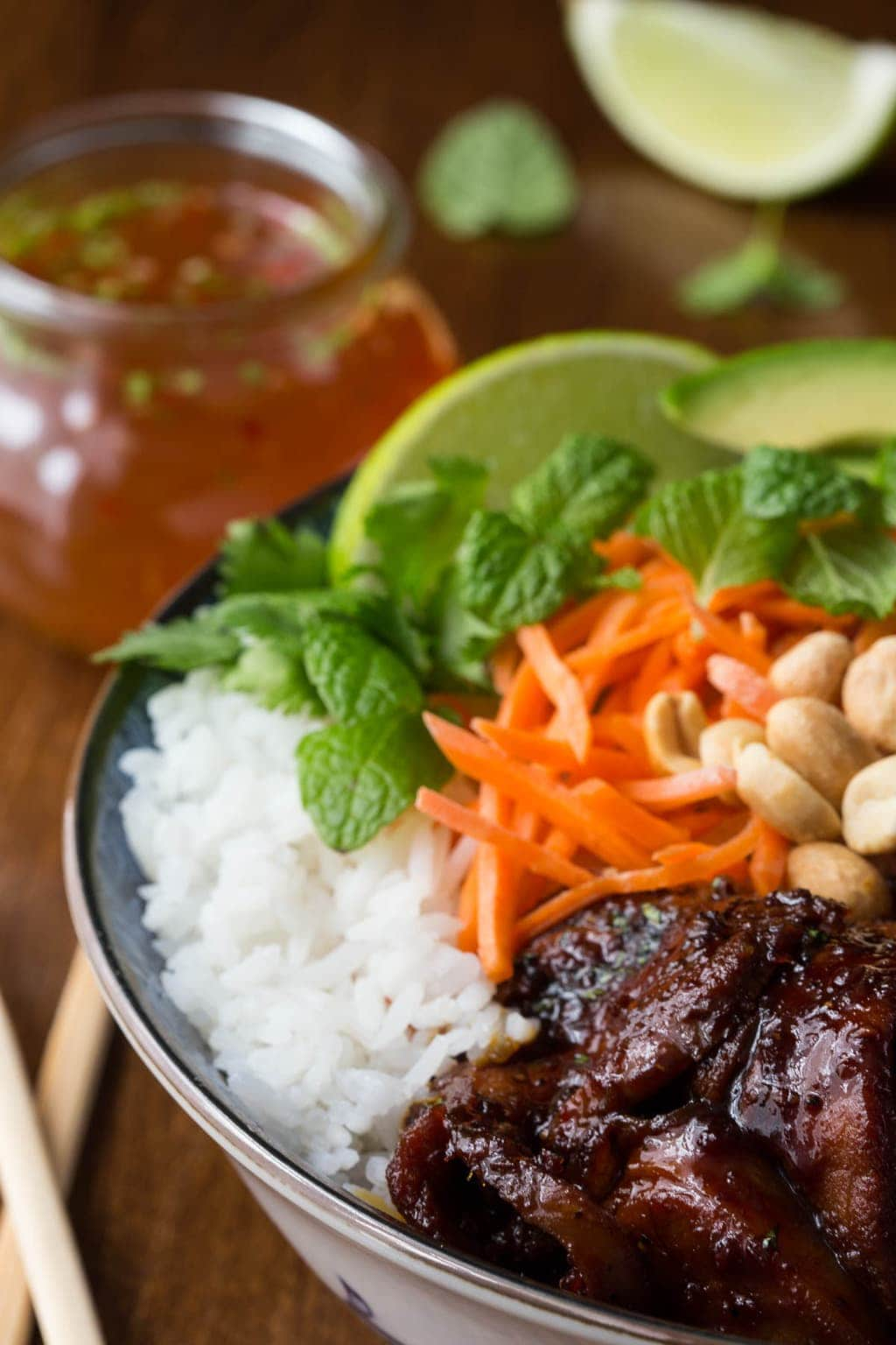 A photo of a bowl of Easy Vietnamese Caramelized Pork on a wood table with lime wedges and a glass jar of traditional Vietnamese dipping sauce surrounding it.