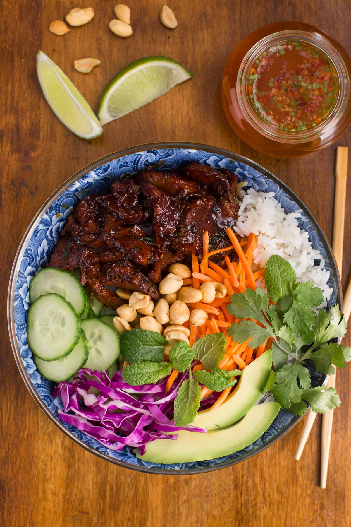 Overhead photo of a plate of Easy Vietnamese Caramelized Pork on a wood table with peanuts, lime wedges and a jar of traditional Vietnamese dipping sauce surrounding it.
