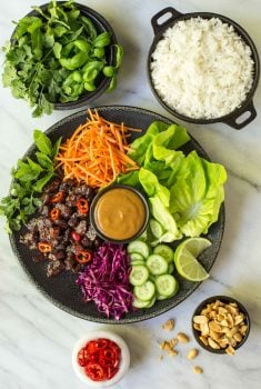 Overhead picture of Vietnamese Carmel Pork Lettuce wraps with toppings and rice on a marble table