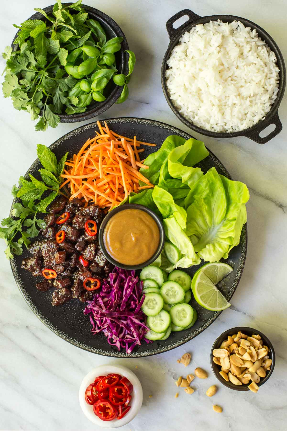 Overhead photo of Vietnamese Caramel Pork Lettuce Wraps on a black plate surrounded by bowls of toppings and rice.