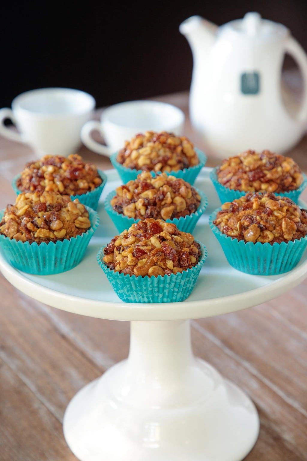 Photo of a white cake stand filled with Walnut Date Banana Muffins in turquoise cupcake liners.