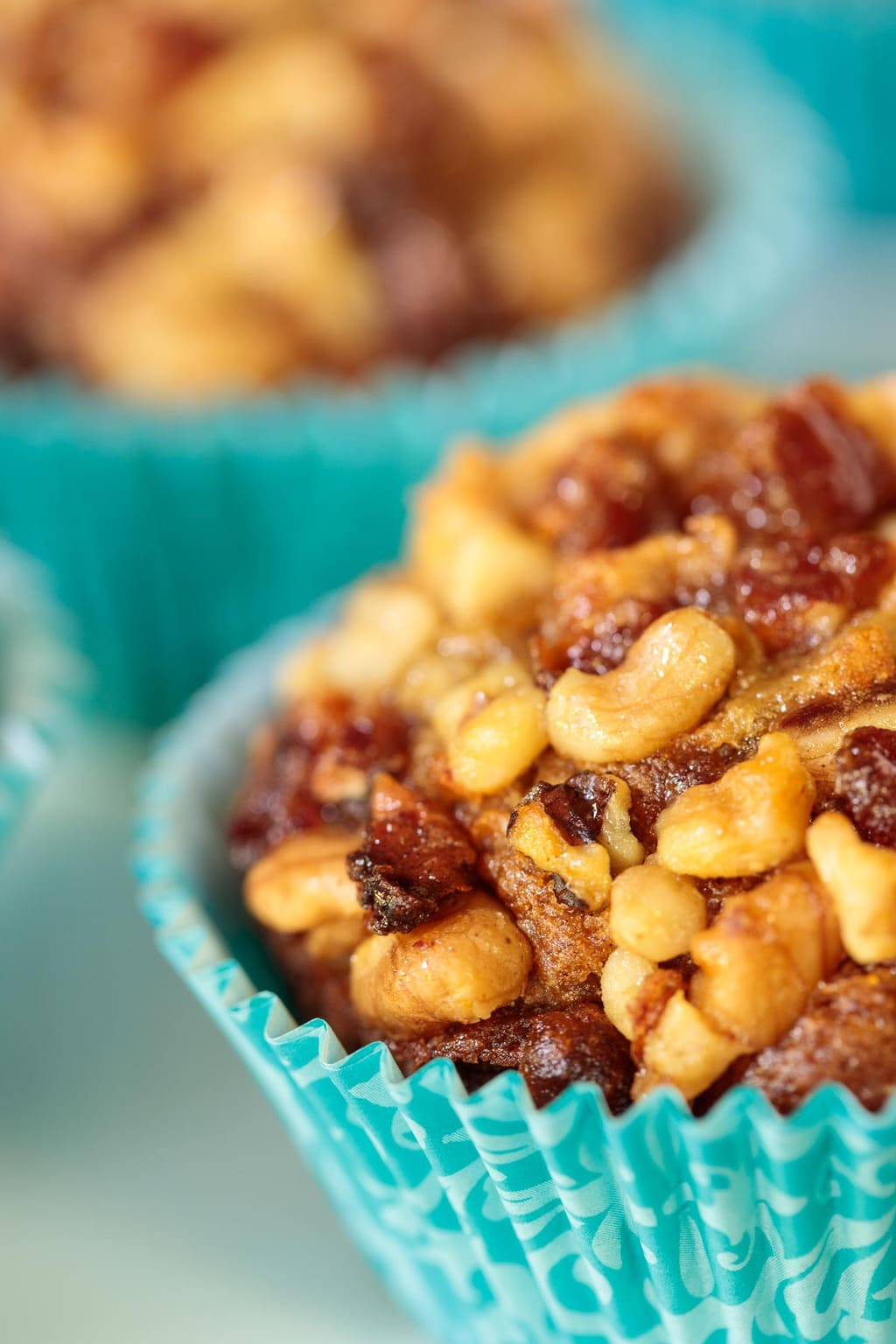 Ultra closeup of a plate of Walnut Date Banana Muffins in turquoise patterned cupcake liners.