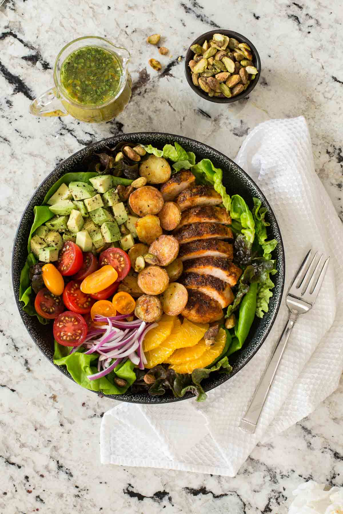Overhead photo of a black plate filled with Warm Chicken and Roasted Potato Salad on a granite countertop.